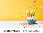 Small photo of A colorful birthday cupcake with seven candles and confetti on a yellow background