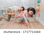 Small photo of little girl boy brother, siblings, friendschild climbs through a rope web, a game obstacle quest indoors. The concept of active play in the home room, quarantine, self-isolation.