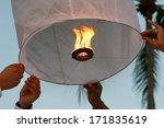 People Releasing A Fire Lantern.