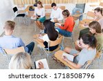 Small photo of Focused group of adult students writing examination while sitting in semicircle in auditorium