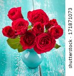 Stock photo bouquet of red roses in a vase on blue wooden background 171871073