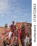 Small photo of BIKANER, RAJASTHAN, INDIA - JANUARY 11, 2020: Indian boy riding on camel during Camel festival in Rajasthan. The Camel Festival begins with a colourful procession of bedecked camels.