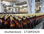 Small photo of The food industry. Glass beer bottles moving on conveyor