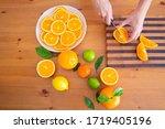 Female Hands Cutting Orange...
