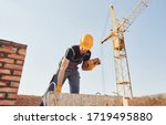 Construction worker in uniform and safety equipment have job on building. - stock photo