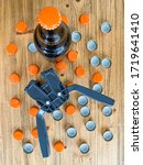 Small photo of Beer brewing at home, plastic capper to put metal caps on bottles, brown glass beer bottle and orange crown caps on wooden background. Vertical image