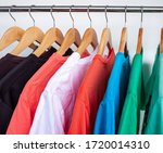 Small photo of Fashion T-shirt on clothing rack - Closeup of bright colorful closet on wooden hangers in store closet