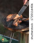 Portable wood-fried grill with grilling meat, a man turns a meat with a knife. Camping grill, smoke, picnic - stock photo