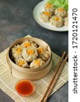 Small photo of Dim Sum in bamboo steamer with sauce and chopstick. Dim sum on plate blurred background. Asian Food