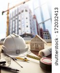 safety helmet blue print plan and construction equipment on engineer working table with building crane construction background use for  real estate and land development theme - stock photo