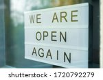 Small photo of Lightbox with as sign we are open again behind a glass door of the cafe. We're open again after quarantine, video of small business owner. Please wear a face mask and keep your distance to protect