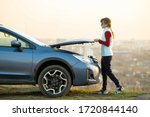 Small photo of Young woman opening bonnet of broken down car having trouble with her vehicle. Female driver standing near auto with popped up hood.