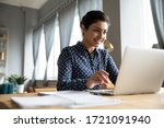 Small photo of Head shot smiling pretty indian girl sitting at table, looking at laptop screen. Happy hindu ethnic woman reading message email with good news, chatting with clients online, working remotely.