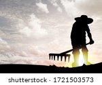 Silhouette Of A Farmer Raking...