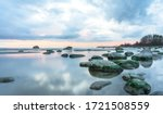 Small photo of Southern coast of the Finnish Gulf. Rocks covered with green seaweed in the Baltic sea. Smooth transparent reflective water. Orange sunset markings under the low altitude clouds. Estonia, Baltic