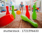 Small photo of children a boy throws ball into a home bowling alley and smashes the bowling pins. Selective focus. concept of active play in the home room, quarantine, self-isolation, achieving goal