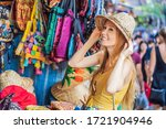Small photo of Coronavirus is over. Quarantine weakened. Take off the mask. Now you can travel. Woman traveler choose souvenirs in the market at Ubud in Bali, Indonesia