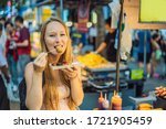 Small photo of Coronavirus is over. Quarantine weakened. Take off the mask. Now you can travel. Young woman tourist eating Typical Korean street food on a walking street of Seoul. Spicy fast food simply found at