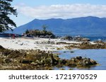 Ocean and mountain scenic views from a remote island beach with white sand and rocky shores at the Broken Group Islands in Pacific Rim National Park - stock photo