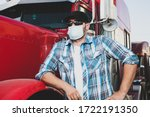Semi truck professional driver on the job in casual clothing wears safety medical face mask. Confident looking trucker stands next to red big rig wearing protection sunglasses and surgical mask. - stock photo