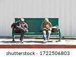 WILMINGTON/CALIFORNIA - APRIL 22, 2020: Two men asleep mid-day on a bus bench while awaiting the local bus'  arrival. Wilmington, California USA  - stock photo