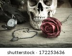 Small photo of Still life with human skull with red rose bud ,metal chain in heart shape and pocket watch