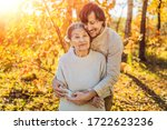 Small photo of Coronavirus is over. Quarantine weakened. Take off the mask. Now you can Meet grandparents - grandmother and grandfather. Grandmother and adult grandson hugging in autumn park