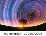 Beautiful night landscape, The camera on the tripod and tree silhouette on the hill under the  colorful star trails on the sky. Night timelapse photography.