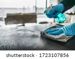 Small photo of Sanitizing surfaces cleaning home kitchen table with disinfectant spray bottle washing surface with towel and gloves. COVID-19 prevention sanitizing inside.
