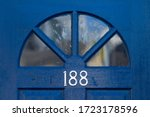 Small photo of House number 188 on a blue wooden front door with a semicircle of glass panels