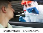 Small photo of Medical UK worker performing drive-thru COVID-19 check,taking nasal swab specimen sample from male patient through car window,PCR diagnostic for Coronavirus presence,doctor in PPE holding test kit