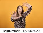 Small photo of Cute Young Woman Light Brown In Striped Pink, Black Shirt On A Yellow Background, Confused Girl Is Afraid, Pulls Away From Problems. Demonstrates The Palms Of Hands. Concept Of Confusion And Infirmity