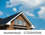 Metal tile roof of brick house against blue sky with clouds