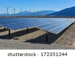 Rows Of Solar Panels And Wind...