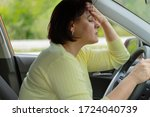 Small photo of Stress and malaise of a woman driving a car. Fatigue on the road. Tired girl in traffic jam