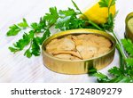Small photo of Appetizing tunny in oil in open tin can on wooden table with fresh parsley and lemon
