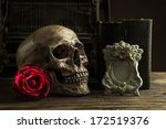 Small photo of Still life with human skull with red rose, old book and telephone on wooden floor