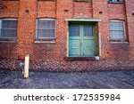 Back side of Abandoned WWII factory with green doors and windows - stock photo