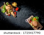 Small photo of Delicious grilled burger with beef, tomatoes, cheese, cucumber and lettuce on a dark background. Top view with copy space. The concept of fast food and junk food