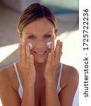 Young Woman Rubbing Skin Cream...