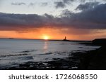 Sunrise At Sea With Lighthouse