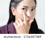 Small photo of Working women has eyes inflammation with iris infection due to macular degeneration from mobile phone and computer. Vitreous and eye floaters. Aged wrinkle eyes. Isolated white background.