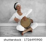 A Smiling Woman Plays A Sitting ...