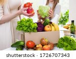 Small photo of Food delivery. Mom and daughter unpack a box of vegetables and fruits. Online order from the grocery store