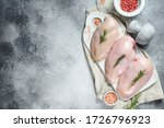 Raw Chicken Breasts On A White...