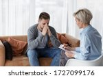 Small photo of Depression Counseling. Desperate Man Telling About Unhappy Life While Professional Psychologist Taking Notes During Appointment In Office. Selective Focus