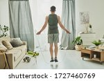 Small photo of Back view of young man in activewear jumping with skipping-rope while standing in front of window of living-room during workout