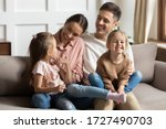 Small photo of Happy young mother and father with two little daughters sitting on couch, looking at each other, family enjoying tender moment, smiling parents and preschool children having fun together
