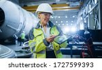 Small photo of Professional Heavy Industry Female Engineer Wearing Safety Uniform, Holds Digital Tablet Computer and Explains Product Design. Industrial Factory Construction of Oil, Gas and Fuels Transport Pipeline