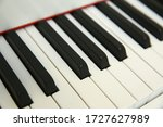 grand piano keyboard with glossy black and white keys as a music background in wide panoramic banner format, selected focus, narrow depth of field - stock photo